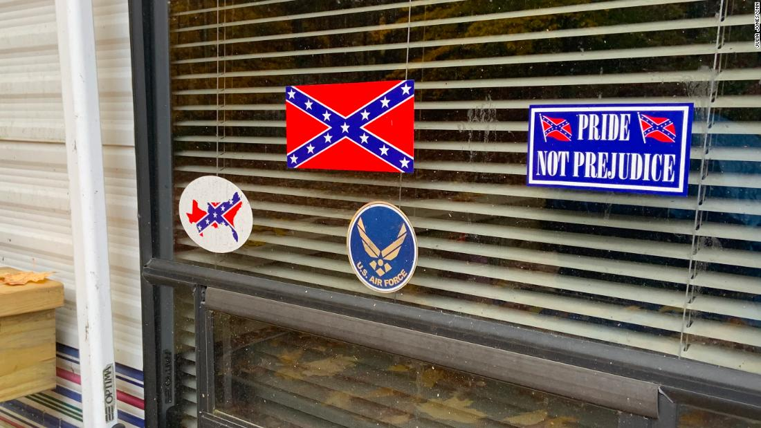 Confederate symbols and a US Air Force sticker adorn a window at the mobile home.
