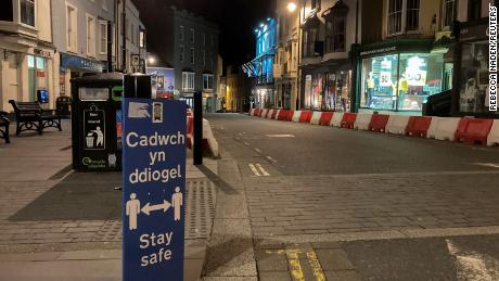 A social distancing sign is seen in an empty street during the first evening of the welsh lockdown, amid the coronavirus disease (COVID-19) outbreak, in Tenby, Wales, Britain October 23, 2020. REUTERS/Rebecca Naden