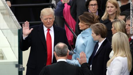 WASHINGTON, DC - JANUARY 20:  Supreme Court Justice John Roberts (2L) administers the oath of office to U.S. President Donald Trump (L) as his wife Melania Trump holds the Bible on the West Front of the U.S. Capitol on January 20, 2017 in Washington, DC. In today's inauguration ceremony Donald J. Trump becomes the 45th president of the United States.  (Photo by Drew Angerer/Getty Images)