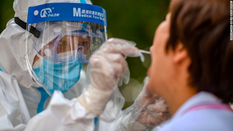 A medical worker collects a swab sample from a resident in Urumqi, Xinjiang during a citywide testing drive in July.