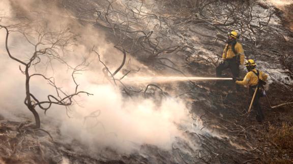 A firefighter uses a hose as the Silverado Fire approaches near Irvine, California.