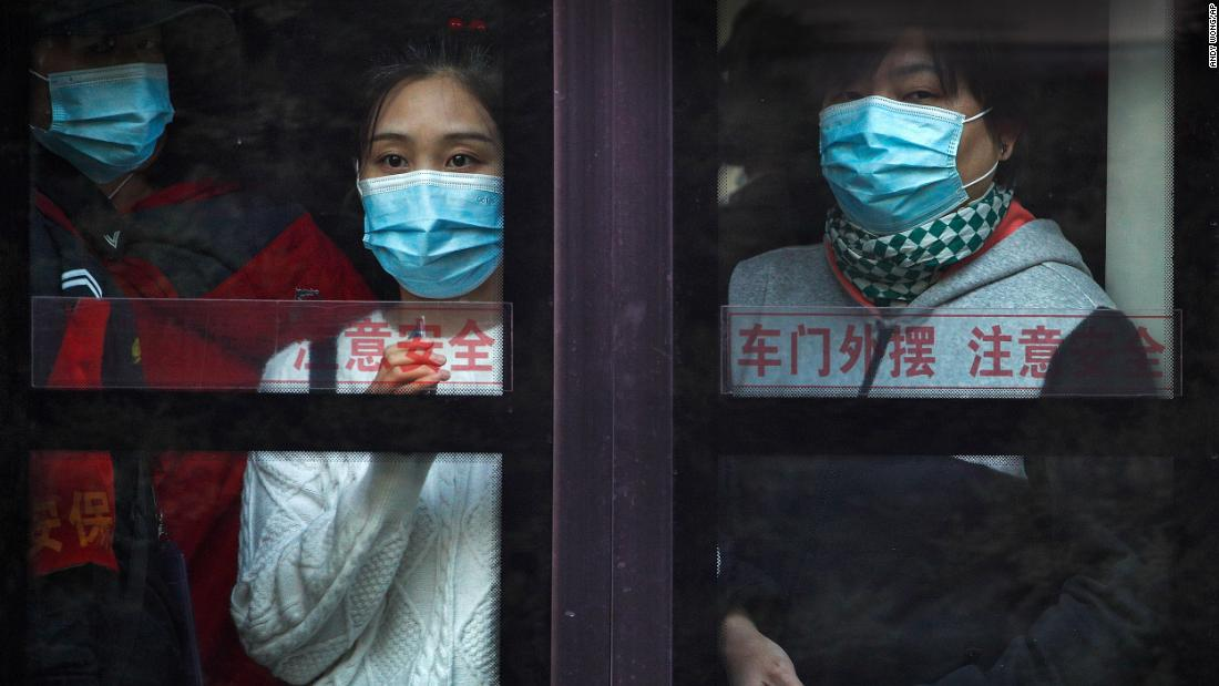 Commuters ride a bus in Beijing during rush hour on Monday, October 26.