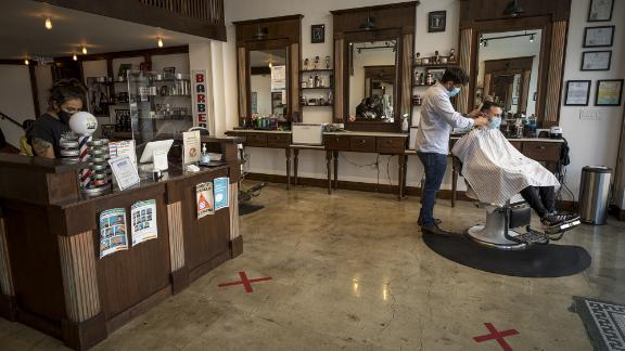 A customer gets a haircut from a stylist wearing a protective mask at a barber shop in San Francisco, California, U.S., on Tuesday, Sept. 15, 2020. Thousands of San Francisco businesses were allowed to reopen Monday following a nearly six-month shuttering, according to the San Francisco Chronicle. Photographer: David Paul Morris/Bloomberg via Getty Images