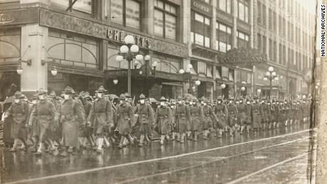 The 39th Regiment marched through the streets of Seattle in December 1918, wearing masks made by Seattle Chapter of the Red Cross.
