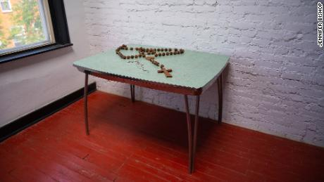 A rosary sits on a table in Rafael Alvarez's home. The room is now filled with donated rosaries.
