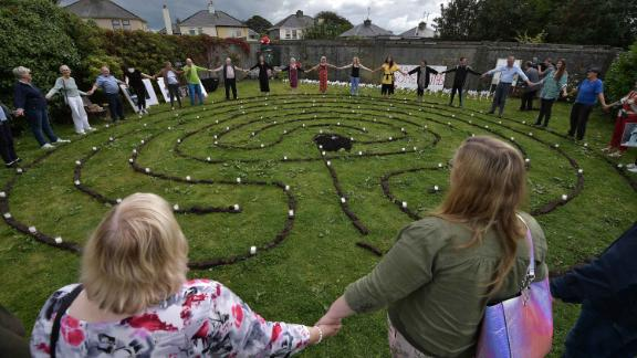 TUAM, IRELAND - AUGUST 25: Relatives and supporters hold hands with survivors as a vigil is held at the Tuam Mother and Baby home mass burial site on August 25, 2019 in Tuam, Ireland. Nearly 800 babies and young children who died in the Tuam Home run by the Bon Secours order of nuns for unmarried mothers are buried there in unmarked graves. The vigil was held to highlight the government's delay in progressing legislation to allow for the excavation of the site, a year after a similiar vigil was held to coincide with the visit of Pope Francis in nearby Knock. The home was one of 10 Irish institutions run by religious orders, to which about 35,000 unmarried pregnant women were sent. It is thought a child died there almost every two weeks between the mid-1920s and 1960s. (Photo by Charles McQuillan/Getty Images)