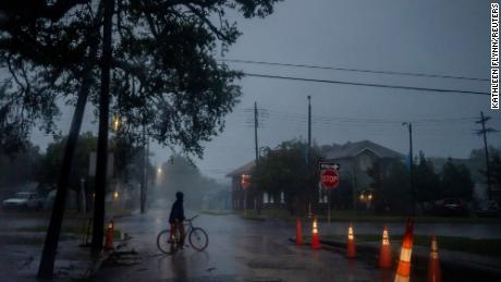 A man walks his bike through heavy wind and rain caused by Hurricane Zeta in New Orleans, Louisiana, U.S., October 28, 2020.  REUTERS/Kathleen Flynn