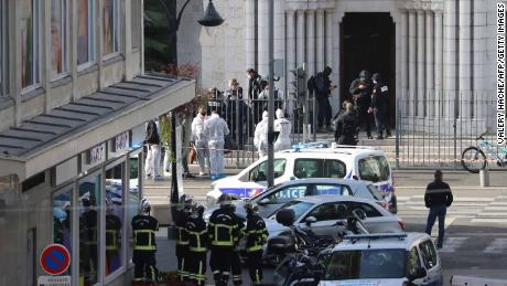 French elite police enter the Basilica of Notre-Dame de Nice as forensics officers wait outside after a knife attack on October 29.