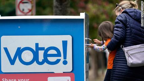 Finley Vong, 3, helps her mother, Tiffany Anderson, drop a ballot into a drop box Wednesday in Seattle.