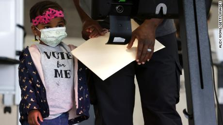 Two-year-old Aissatou Barry accompanies her father at an early voting center at Union Market Tuesday in Washington, DC.