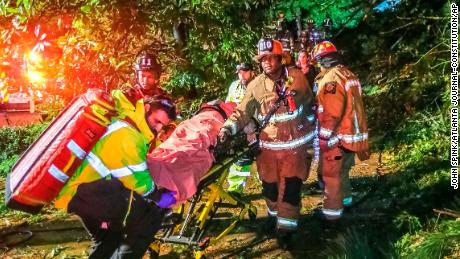 Atlanta firefighters transport a man they freed who was trapped in his third-floor bedroom after a tree came down on a home Thursday.