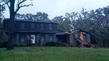 A fallen tree is seen on a home damaged by Zeta Thursday in Lincoln, Alabama.
