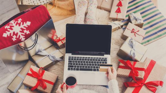 Christmas online shopping top view. Female buyer with laptop, copy space on screen. Woman buys presents in internet with gold credit card, drinks coffee among gift boxes. Winter holidays sales
