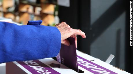 A woman places her referendum voting paper in the ballot box as advance voting begins on October 3 in Wellington, New Zealand.