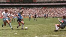 Maradona runs past English defender Terry Butcher (left) on his way to beating goalkeeper Peter Shilton (right) and scoring his second goal against England in the World Cup in 1986.