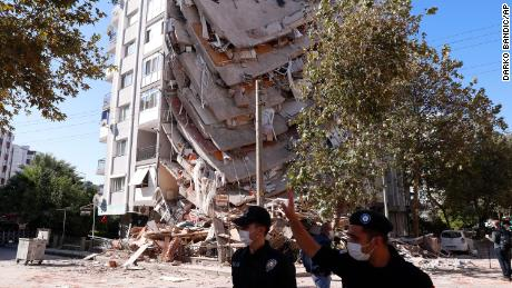 Members of security forces walk past a collapsed building in Izmir, Turkey, on Saturday.