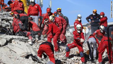 Members of rescue services search the debris of a collapsed building for survivors in Izmir, Turkey, on Sunday.