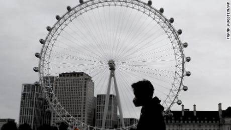 A man wearing a mask passes the London Eye on Thursday as England prepares for a month-long lockdown.