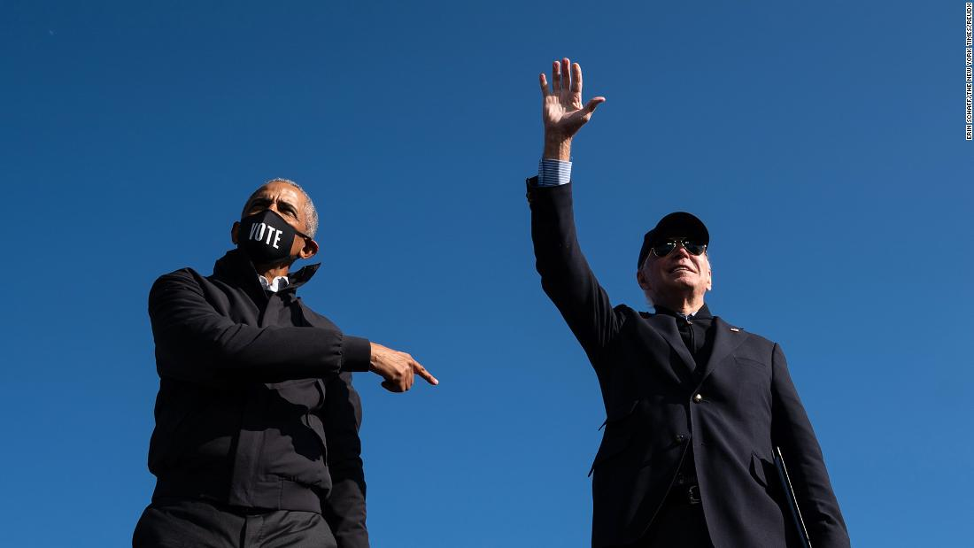 Former President Barack Obama points to Biden after speaking at a drive-in rally in Flint, Michigan, on October 31.