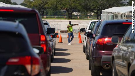 An election worker guides voters in cars at a drive-through mail ballot drop-off site at NRG Stadium in Houston, Texas, last year.