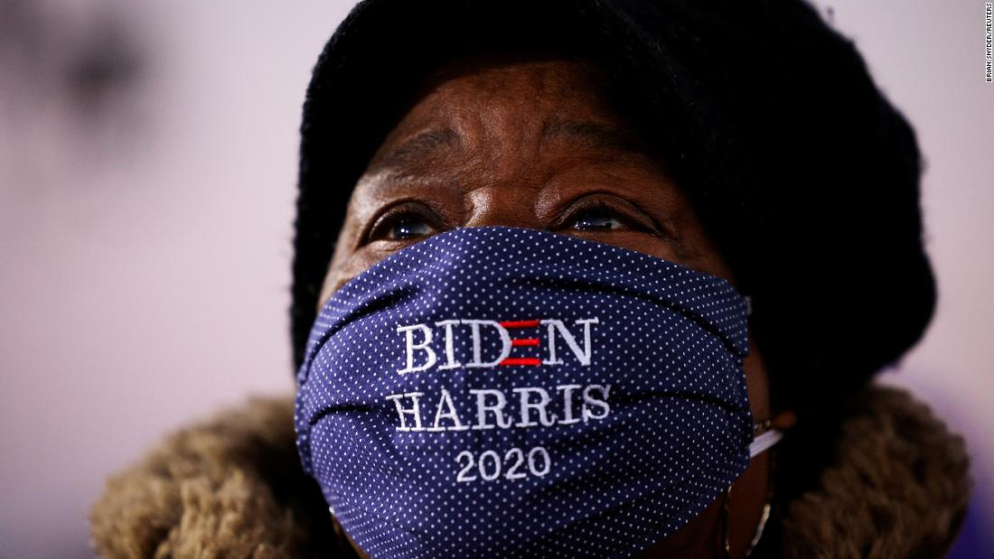 A woman watches Biden speak at a drive-in event in Detroit on Saturday, October 31.