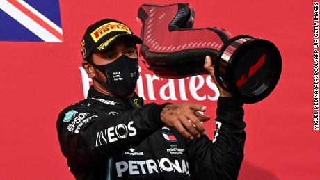 Hamilton holds his trophy as he celebrates on the podium after the Emilia Romagna GP.