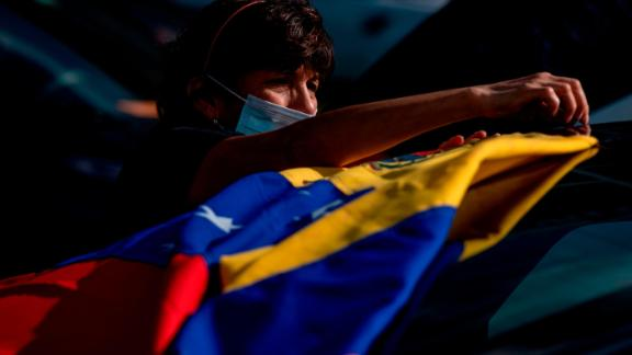 A supporter attaches the Venezuela national flag to her car before the former US President Barack Obama arrival at a Biden-Harris drive-in rally in Orlando, Florida on October 27, 2020. (Photo by Ricardo ARDUENGO / AFP) (Photo by RICARDO ARDUENGO/AFP via Getty Images)