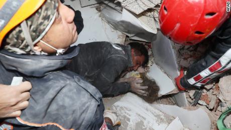 Un secouriste berce le visage de la fillette de 2 ans au milieu des efforts pour la sortir des décombres.