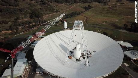 A 400-ton crane lifts the new X-band cone into the 70-meter (230-feet) Deep Space Station 43 dish located in Canberra, Australia. The antenna is the only one that can issue commands to NASA's Voyager 2 probe in interstellar space.