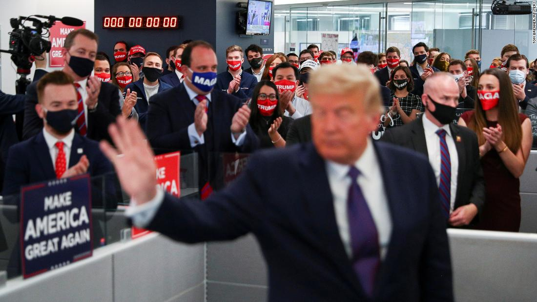 President Donald Trump is applauded by his campaign staff as he visits his campaign headquarters in Arlington, Virginia, on Tuesday, November 3.
