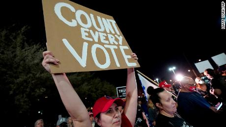"A supporter of President Donald Trump holds a ""Count every vote"" sign at a rally Wednesday night outside the Maricopa County vote counting center in Phoenix."