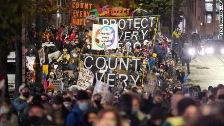 Protesters representing Black Lives Matter and Protect the Results march Wednesday night in Seattle.