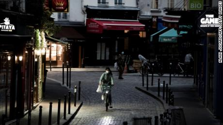 A woman rides a bike along an empty street in the district of St. Michel in Paris on November 3, the fifth day of France's lockdown.