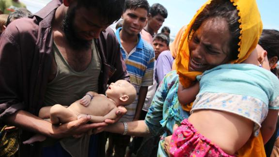 Rohingya refugees fleeing Myanmar hold their infant son Abdul Masood, who died when their boat capsized before reaching Bangladesh on September 13.
