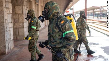 Military officers wearing protective suits and masks disinfect Irun train station in northern Spain on March 28, 2020.