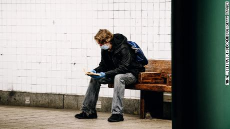 A commuter reads a book while waiting on a Brooklyn subway station platform.