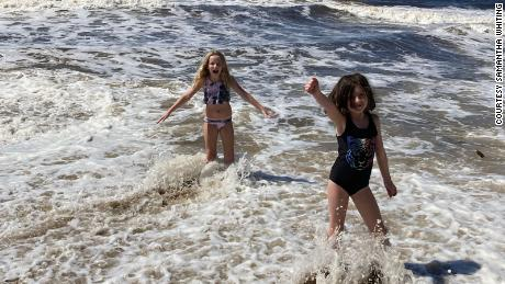 Haylee, left, plays with sister Maddie in the surf.