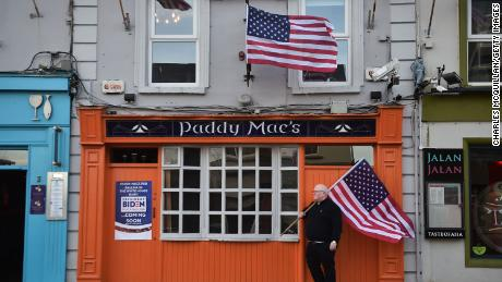 Bar owner Paddy Macs, Michael Carr, stands outside his pub with an American flag on November 7, 2020.