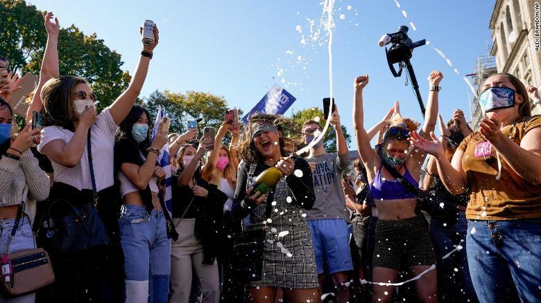 Amanda Madden sprays champagne as people celebrate at Black Lives Matter Plaza on November 7, 2020.