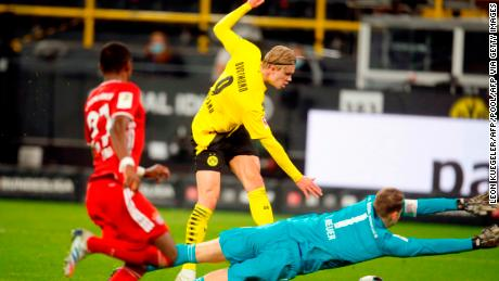 Dortmund's Norwegian forward Erling Braut Haaland (C) scores Dortmund's second goal in the 3-2 defeat by Bayern Munich.