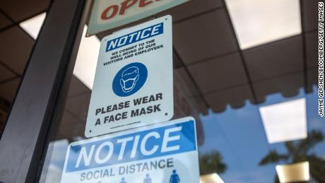 Signs reminding the public to practice social distancing and wear a mask on a storefront in Miami, Wednesday, November 4.