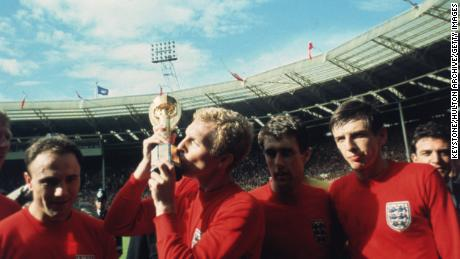England captain Bobby Moore kisses the Jules Rimet trophy as the team celebrates winning the 1966 World Cup final.