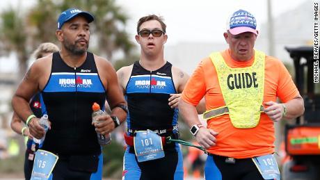 Chris Nikic y su guía Dan Grieb, a la derecha, compiten en el circuito de carreras del Ironman Florida.