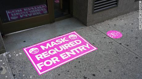 A 'mask required for entry' sign is displayed at the entry to a retail store on August 23, 2020 in New York City.