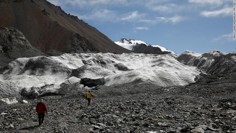 Jin Zizhen, 27, a PhD student of glacial hydrology, and Qin Xiang, the director of the Qilian Shan Station of Glaciology and Ecologic Environment of the Chinese Academy of Sciences, walk towards the Laohugou No. 12 glacier in the Qilian mountains, in Gansu province, China on September 26, 2020.