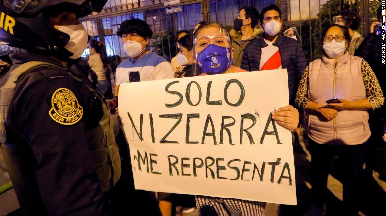 A woman displays a banner reading 'Only Vizcarra represents me' in Spanish as former President Vizcarra arrives home in Lima on November 9.