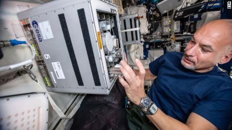 European Space Agency astronaut Luca Parmitano on the International Space Station is shown here conducting the experiment with the biomining reactors.
