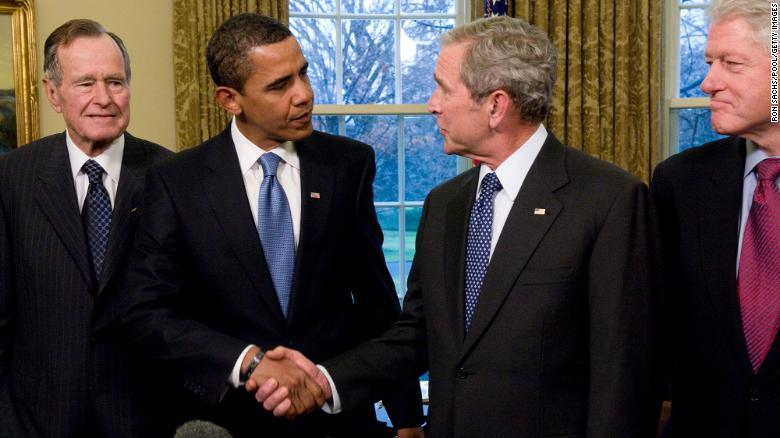 En esta fotografía de archivo del 7 de enero de 2009, el presidente George W. Bush le da la mano en la Oficina Oval al presidente electo Barack Obama mientras los ex presidentes Bill Clinton y George HW Bush observan.