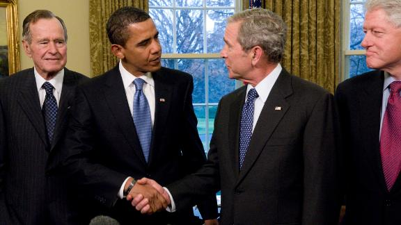 In this January 7, 2009, file photo, President George W. Bush shakes hands in the Oval Office with President-elect Barack Obama as former Presidents Bill Clinton and George H.W. Bush look on.