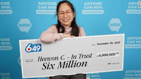 Heewon (Theresa) Choi holds up a check for $6 million after she and three of her coworkers won big on October 31, 2020.